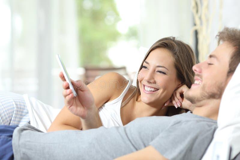 Paar die een slimme telefoon op het bed delen stock afbeeldingen