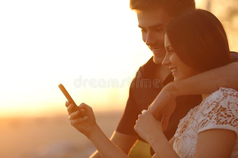 Paar die een smartphone in een zonsondergang achterlicht gebruiken royalty-vrije stock afbeeldingen