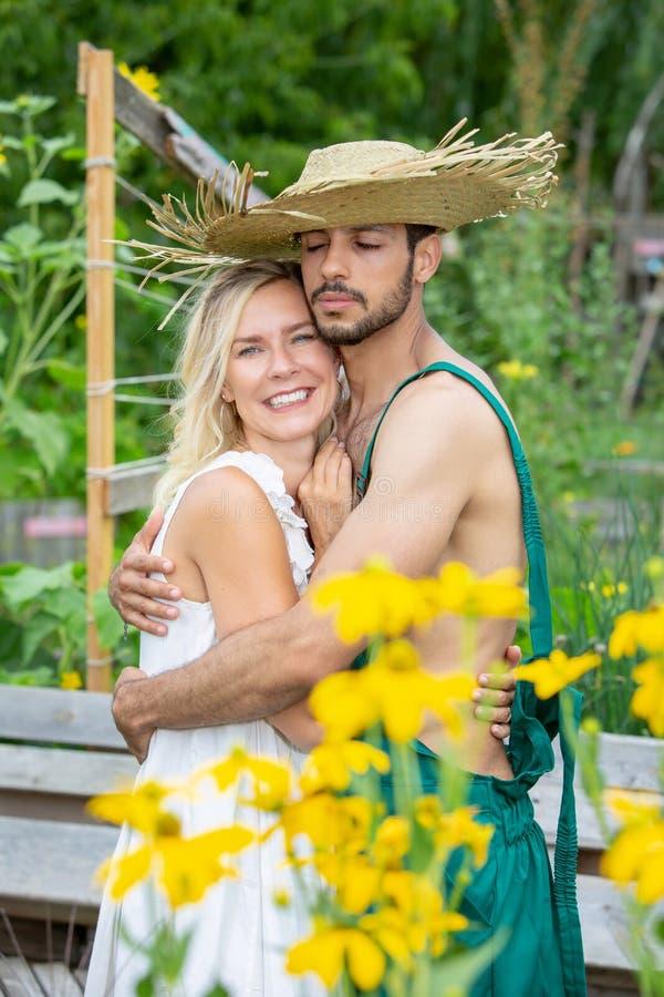 Paar die elkaar buiten in de tuin koesteren royalty-vrije stock afbeelding