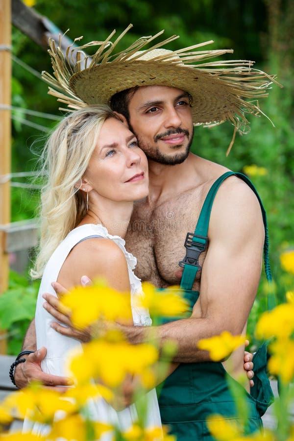 Paar die elkaar buiten in de tuin koesteren stock foto