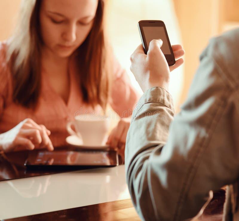 Paar die elkaar negeren bezig met hun mobiele apparaten royalty-vrije stock afbeeldingen