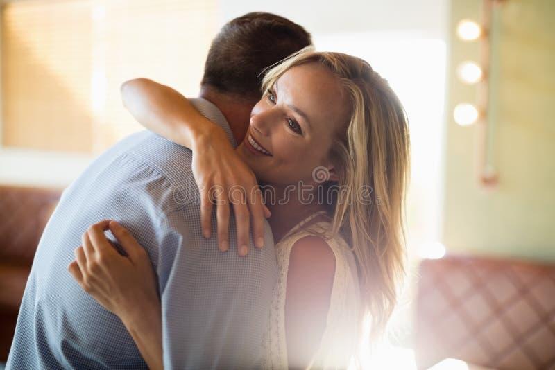 Paar die elkaar in restaurant omhelzen stock foto's