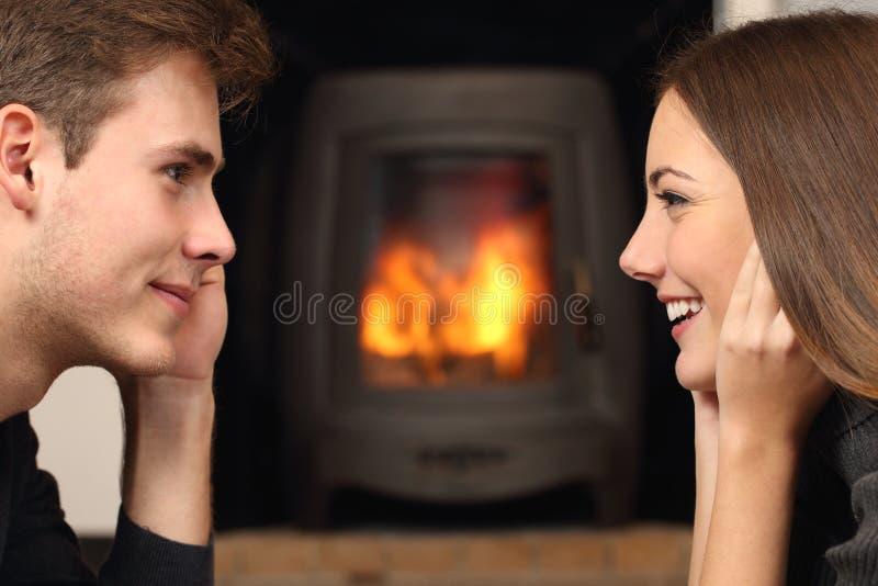 Paar die elkaar vooraan een open haard kijken stock fotografie