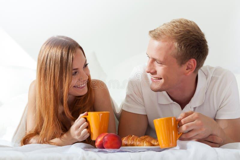 Paar die en in bed babbelen eten stock foto