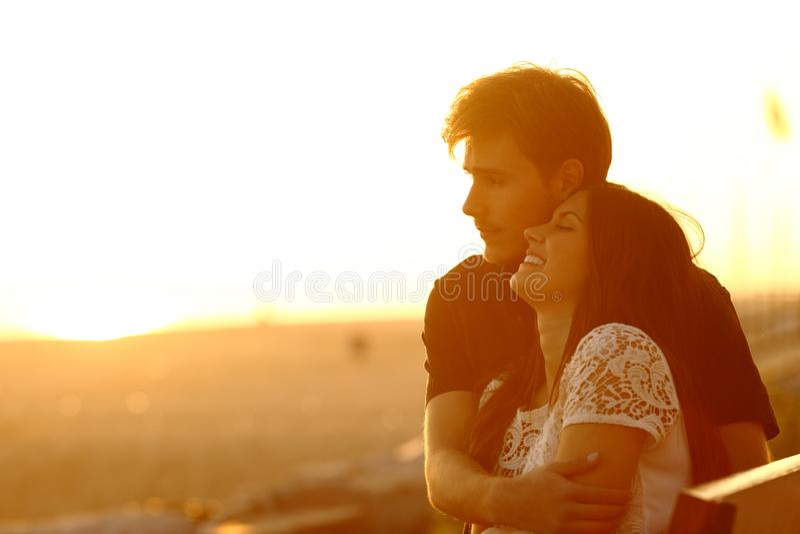 Paar die en bij zonsondergang op het strand dateren flirten royalty-vrije stock afbeelding
