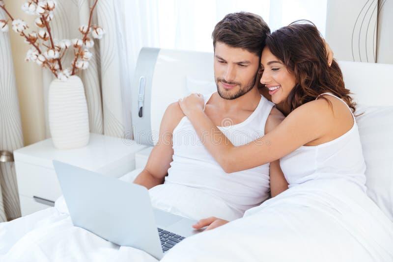 Paar die en een computer koesteren met behulp van die op hun bed liggen stock foto