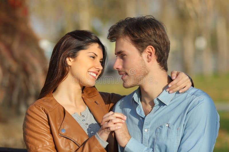 Paar die en in een park koesteren dateren die elkaar kijken royalty-vrije stock afbeelding