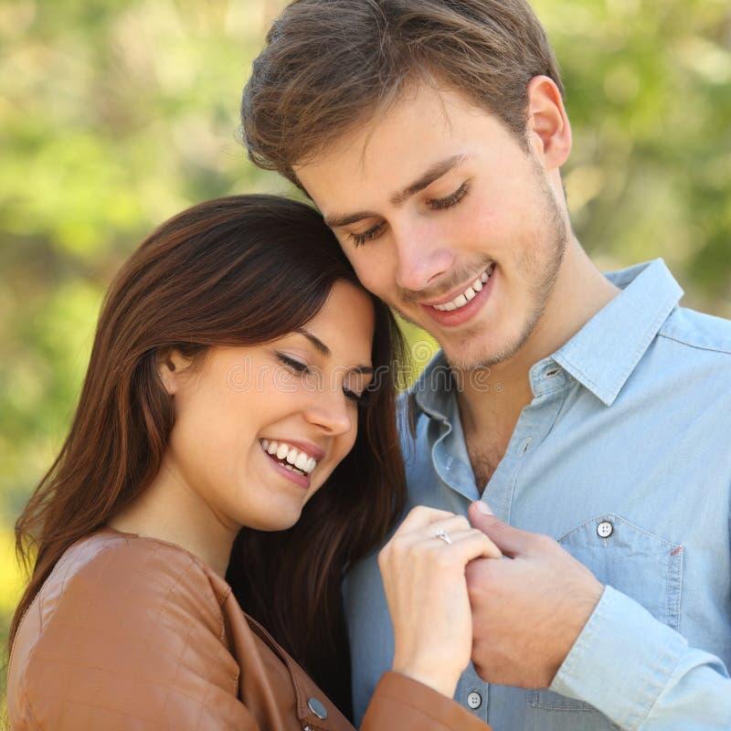 Paar die en handen koesteren houden terwijl blikken een verlovingsring stock afbeeldingen