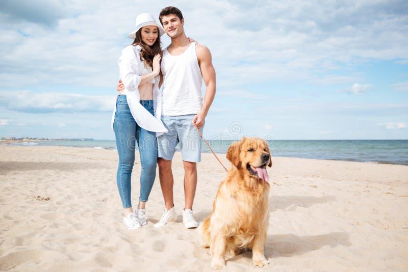 Paar die en met hond op het strand koesteren lopen stock fotografie