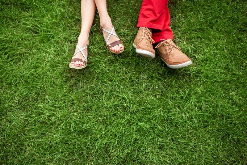 Paar die en op het gras liggen ontspannen stock afbeeldingen