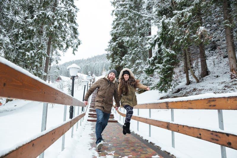 Paar die en samen in de winter springen lopen royalty-vrije stock fotografie