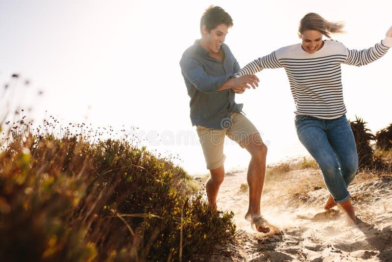 Paar die en van pret op het strand genieten hebben royalty-vrije stock afbeelding