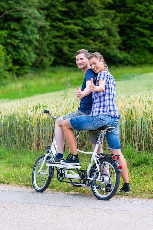 Paar die fiets achter elkaar samen in het land berijden stock foto