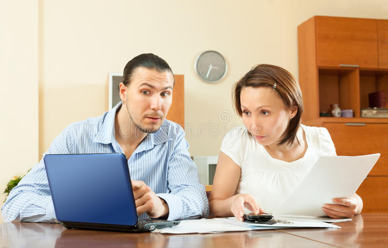 Paar die financiële documenten in laptop kijken royalty-vrije stock foto's