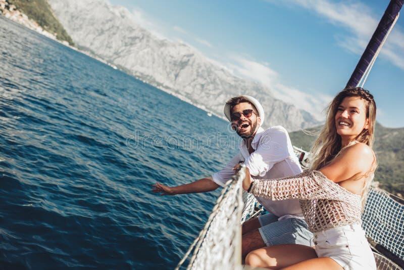 Paar die gelukkige tijd op zee doorbrengen aan een jacht Luxevakantie op een seaboat royalty-vrije stock afbeeldingen