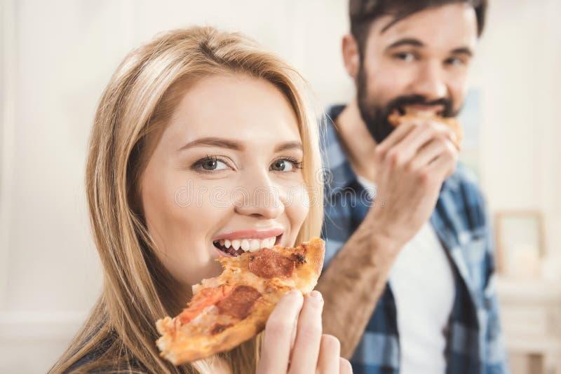 Paar die heerlijke pizza eten stock afbeelding