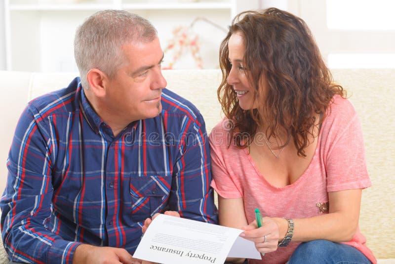 Paar die het contract van de bezitsverzekering ondertekenen royalty-vrije stock afbeelding