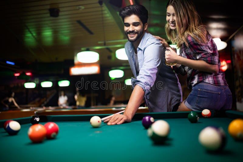 Paar die, het flirten en het spelen biljart in een bar dateren royalty-vrije stock foto's