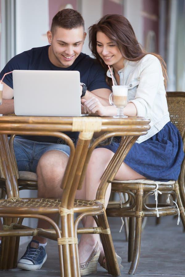 Paar die het notitieboekjescherm bekijken bij een koffie royalty-vrije stock foto