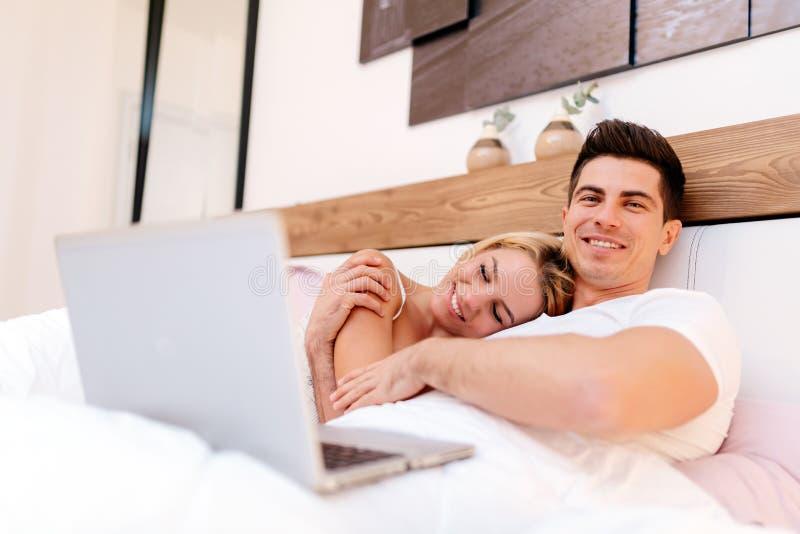 Paar die het Web van bed in ochtend surfen royalty-vrije stock foto