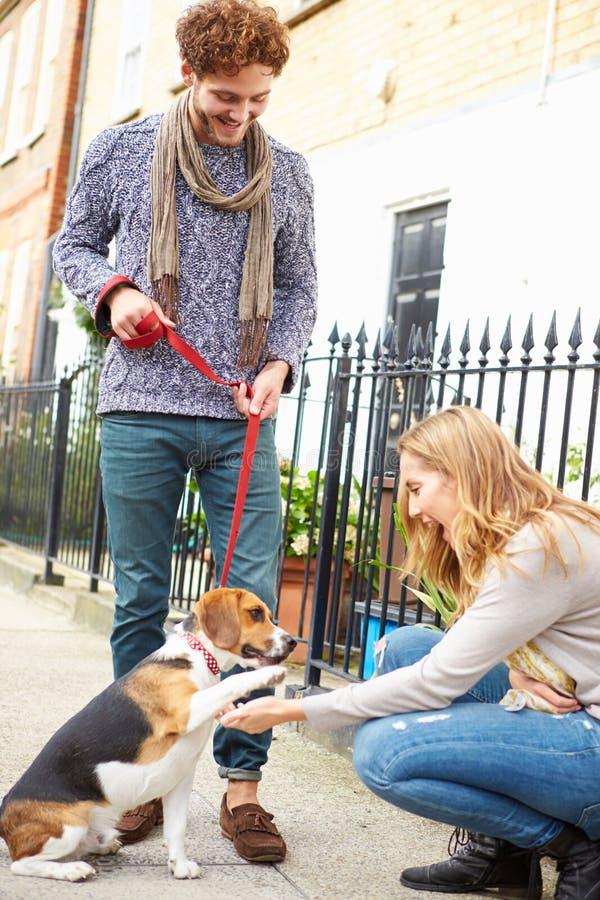 Paar die Hond voor Gang op Stadsstraat nemen stock afbeeldingen