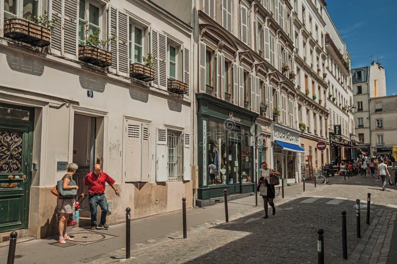 Paar die huis met wandelwagen in bezige steeg van Montmartre verlaten in Parijs royalty-vrije stock afbeeldingen