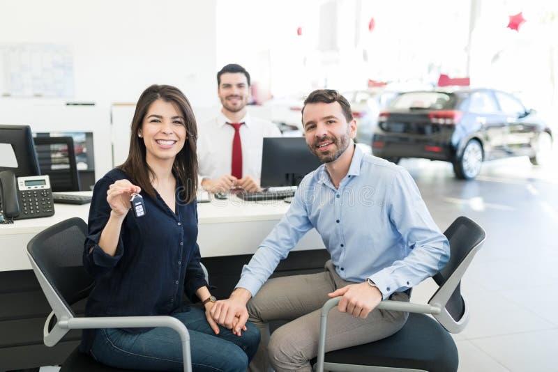 Paar die Hun Opwinding tonen terwijl het Kopen van Eerste Auto stock foto's