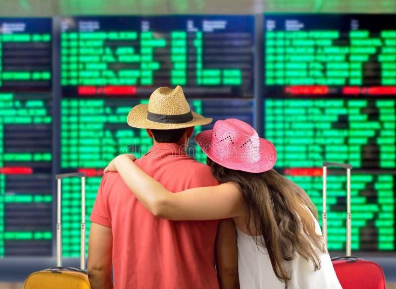 Paar die hun vlucht bij de raad zoeken stock foto's