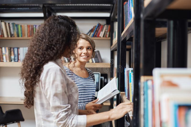 Paar die jonge mooie meisjes in toevallige modieuze kleren die zich dichtbij boekenrekken in bibliotheek bevinden, elkaar bekijke stock foto's