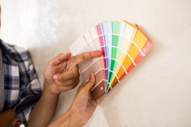 Paar die kleur voor daar het schilderen van nieuw huis kiezen royalty-vrije stock afbeelding