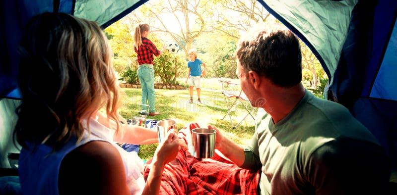 Paar die koffie hebben en jonge geitjes bekijken die buiten de tent spelen stock afbeeldingen