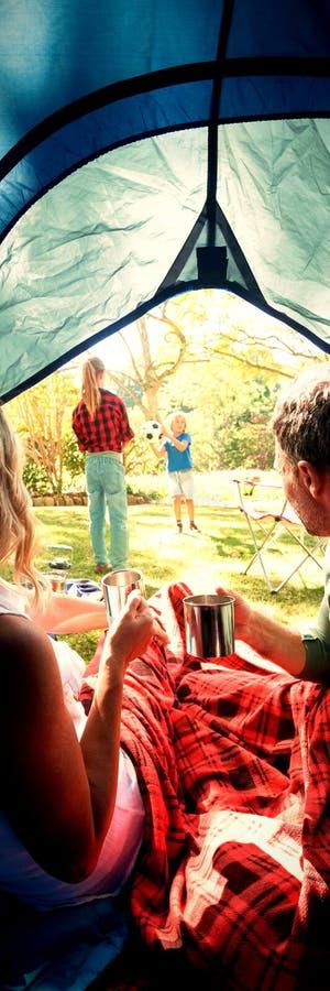 Paar die koffie hebben en jonge geitjes bekijken die buiten de tent spelen royalty-vrije stock foto's