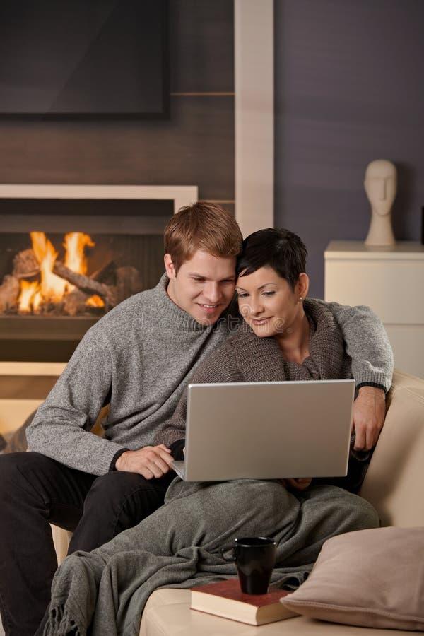 Paar die laptop met behulp van bij de winter stock afbeeldingen