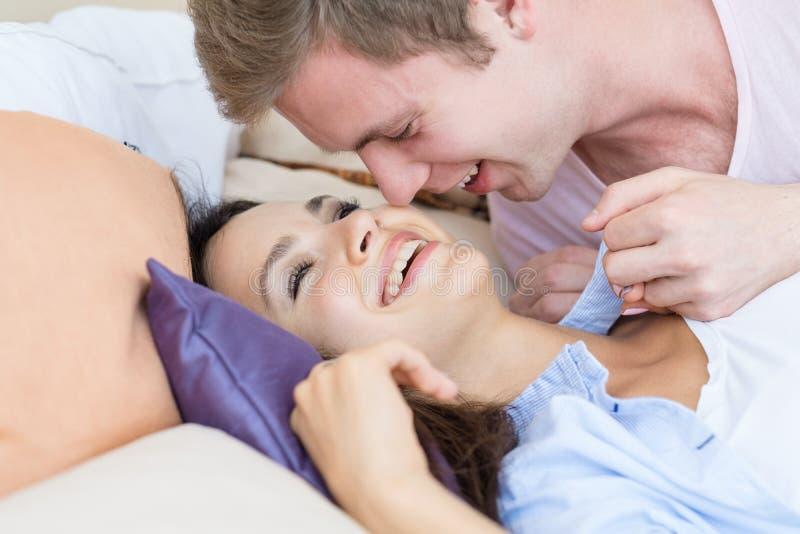 Paar die leggend de verhoudingsband van de bedliefde lachen stock afbeelding