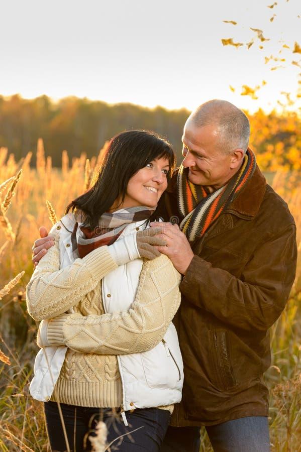 Paar die in liefde in de herfstplatteland koesteren stock foto