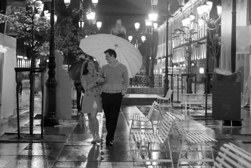Paar die in liefde in de regen lopen stock foto