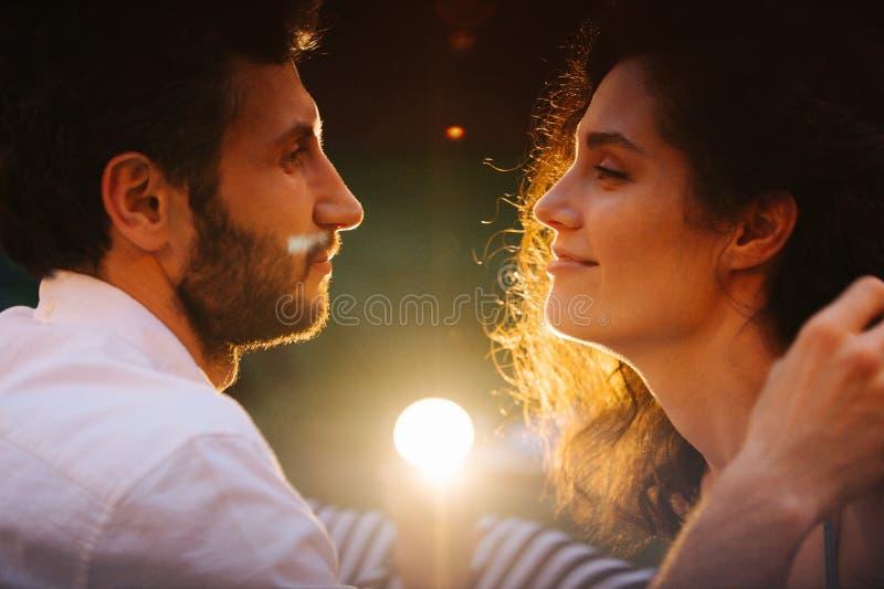 Paar die in liefde elkaar met seksuele die hartstocht, affectie bekijken, door lamp wordt aangestoken stock fotografie