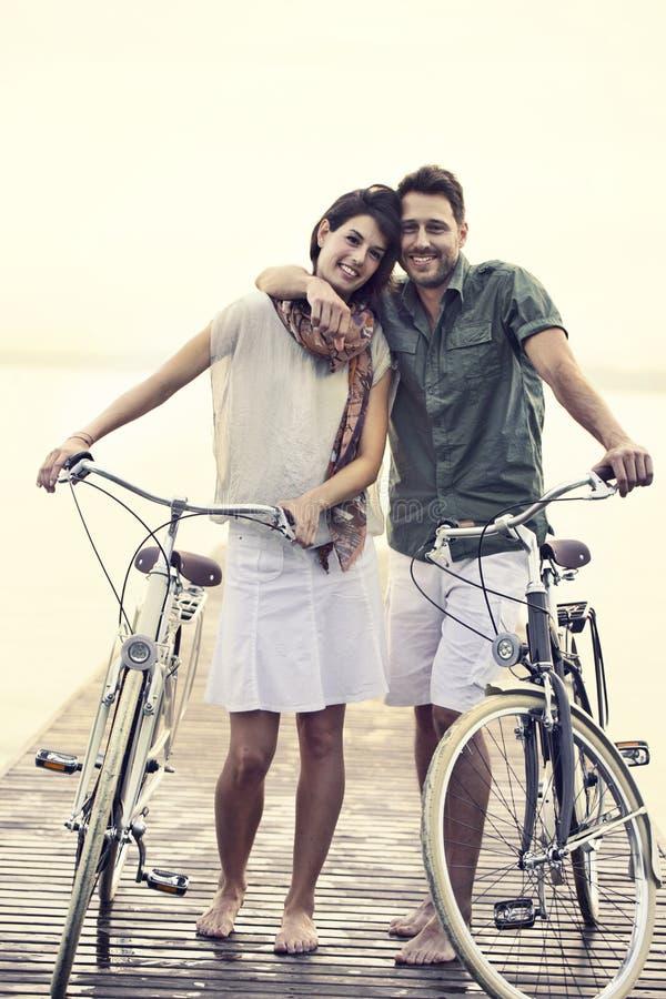 Paar die in liefde hun fiets samen op een promenade duwen stock afbeeldingen