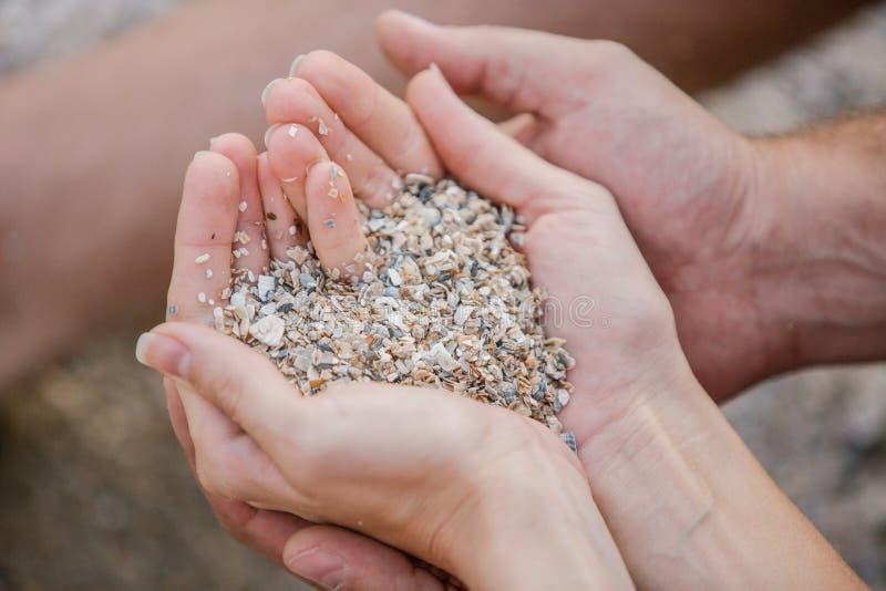 Paar die in liefde, mannelijke en vrouwelijke Handen een zand in vorm van het hart houden royalty-vrije stock afbeeldingen