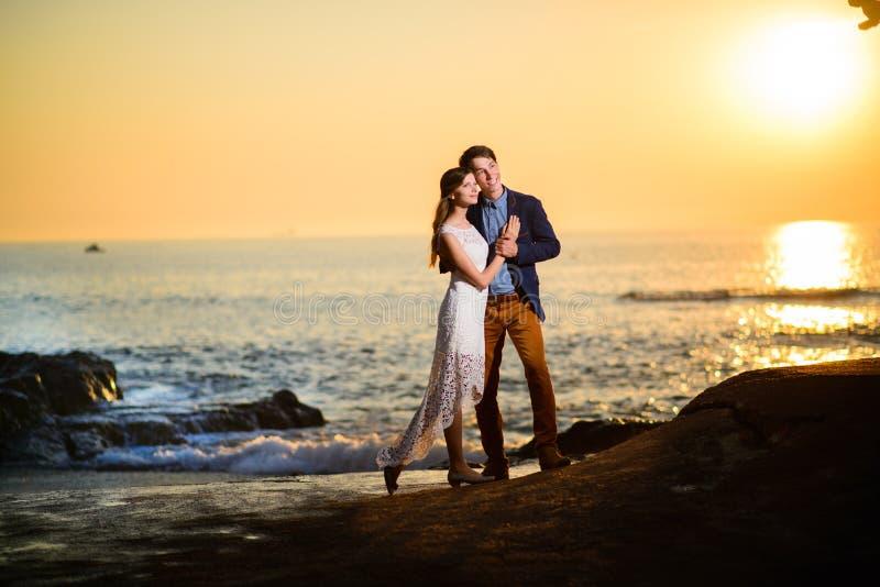 Paar die in liefde op een zonsondergang op het strand letten royalty-vrije stock afbeelding