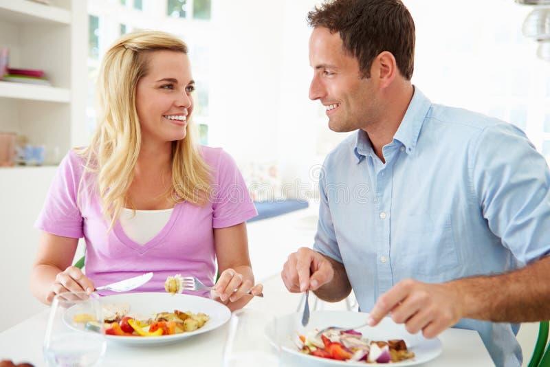Paar die Maaltijd thuis samen eten royalty-vrije stock afbeelding