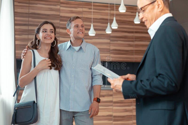 Paar die makelaar in onroerend goed bekijken die documenten voor het kopen van huis voorbereiden stock foto