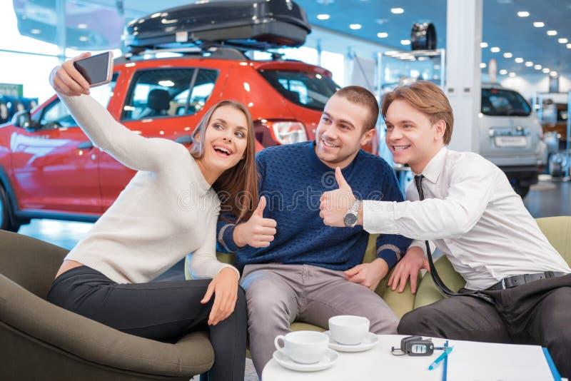 Paar die met de verkoper in toonzaal communiceren royalty-vrije stock afbeelding