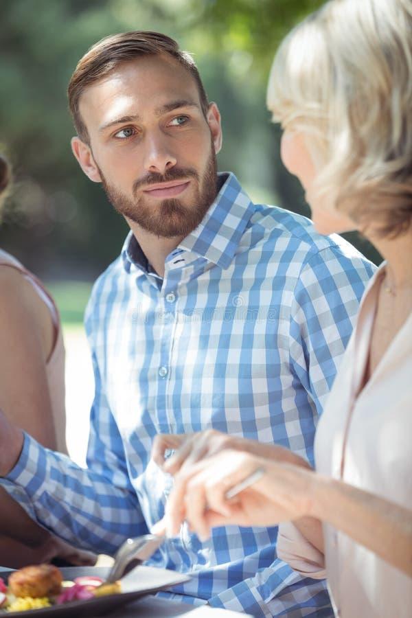 Paar die met elkaar interactie aangaan terwijl het hebben van maaltijd stock afbeelding