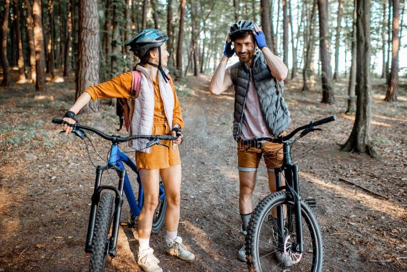 Paar die met fietsen in het bos reizen royalty-vrije stock afbeelding