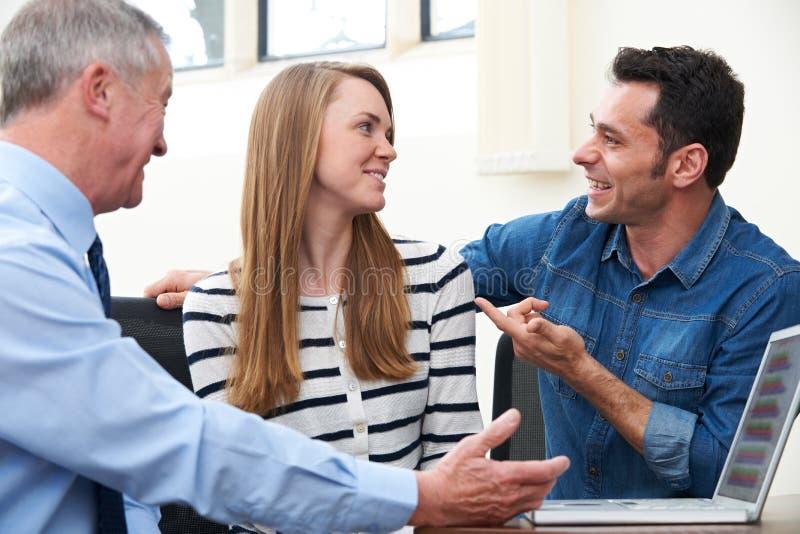 Paar die met Financiële Adviseur in Bureau spreken stock fotografie