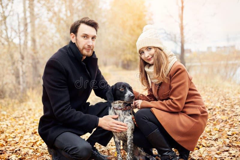 Paar die met hond in het Park en het koesteren lopen De mensen van de de herfstgang royalty-vrije stock fotografie