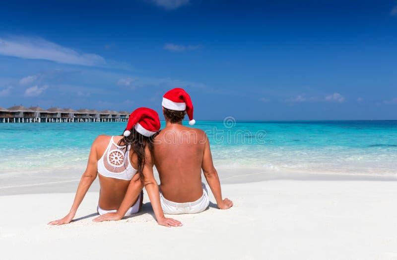 Paar die met Kerstmishoeden op een tropisch strand zitten royalty-vrije stock afbeelding