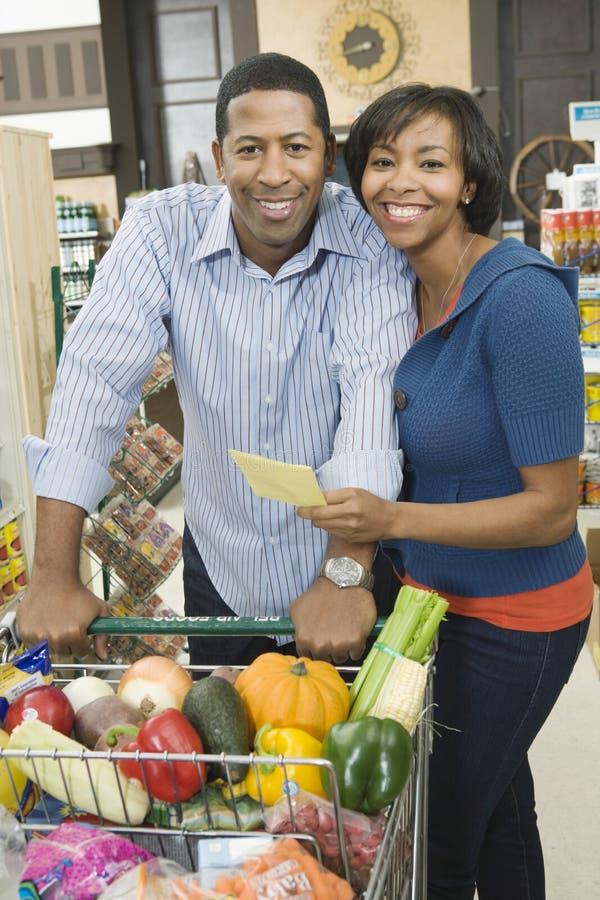 Paar die met Kruidenierswinkel in Supermarktdoorgang winkelen royalty-vrije stock fotografie