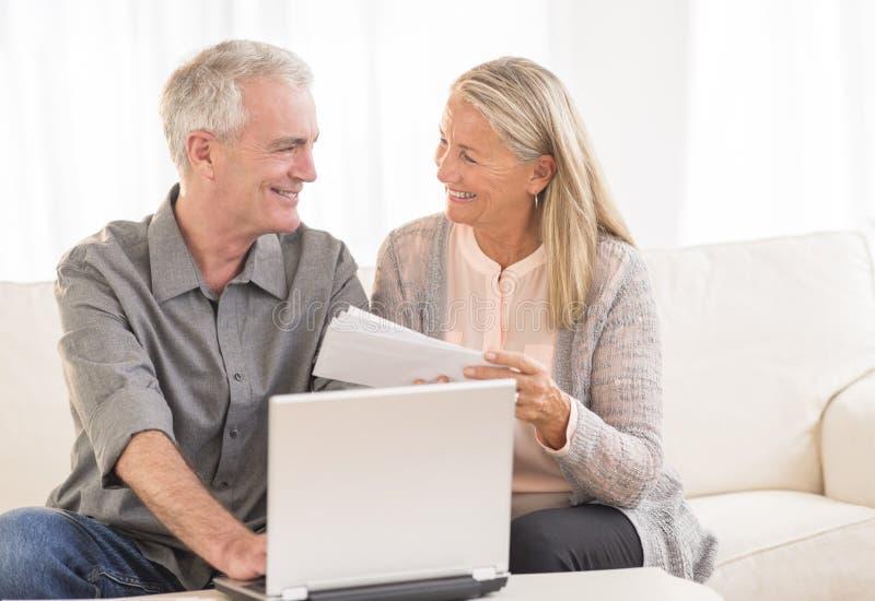 Paar die met Laptop Rekeningen online thuis betalen stock fotografie